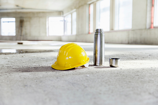 Coffee Break「Thermos flask and hard hat on concrete floor on construction site」:スマホ壁紙(4)