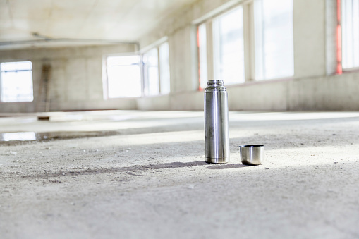 Surface Level「Thermos flask on concrete floor on construction site」:スマホ壁紙(19)