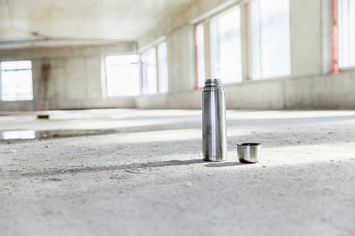 Coffee Break「Thermos flask on concrete floor on construction site」:スマホ壁紙(4)