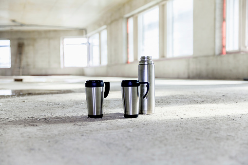 Coffee Break「Thermos flask and mugs on concrete floor on construction site」:スマホ壁紙(13)