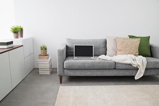 毛布「Opened laptop on couch at modern living room」:スマホ壁紙(8)