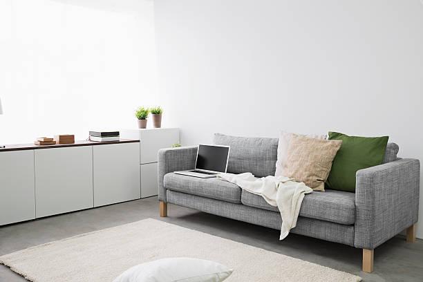 Opened laptop on couch at modern living room:スマホ壁紙(壁紙.com)