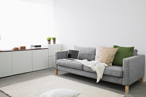 Living Room「Opened laptop on couch at modern living room」:スマホ壁紙(3)