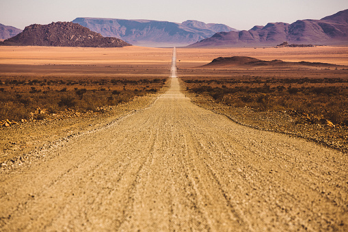Depression - Land Feature「Beautiful empty dirt road in desert plain with mountains in background」:スマホ壁紙(2)