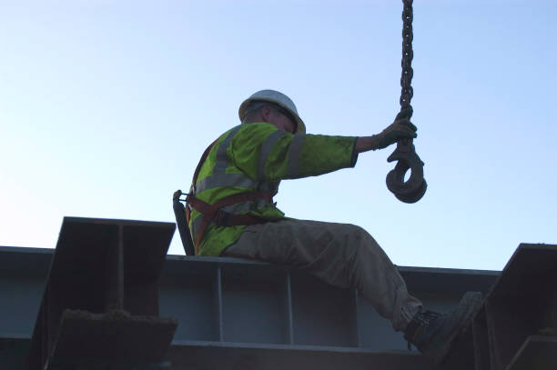 Silhouette of a construction worker in safety equipment securing a hook at heights:ニュース(壁紙.com)