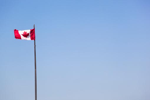 かえでの葉「Canadian flag against blue sky」:スマホ壁紙(7)