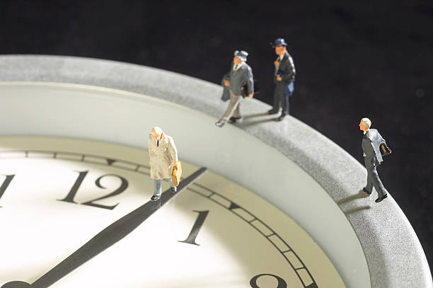 Businessmen figurines walking on a clock:スマホ壁紙(壁紙.com)