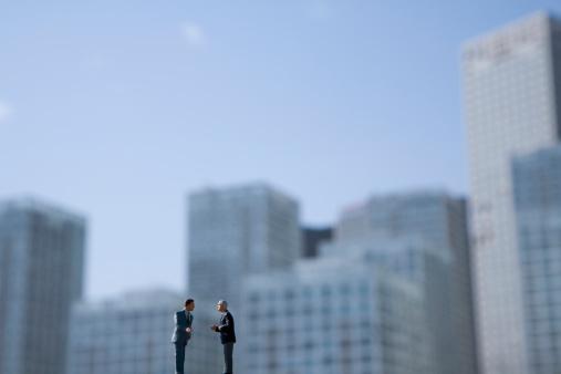 Figurine「China, Beijing, Two miniature figure businessmen with skyline in background」:スマホ壁紙(2)
