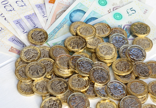 Finance and Economy「Pile of one pound coins in close-up with pound notes.」:スマホ壁紙(11)