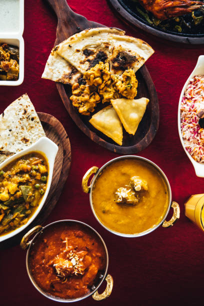 Indian feast with butter chicken, chicken tandoori, lamb curry, vegetable curry, samosas, pakoras, bhajis, naan bread and basmati rice on a table. North Indian food:スマホ壁紙(壁紙.com)