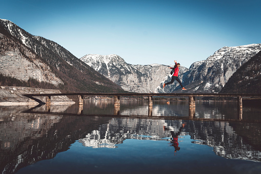 Dachstein Mountains「Woman jumping on a bridge over the lake in the Alps」:スマホ壁紙(3)