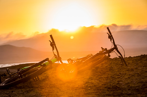 Leisure Activity「Two bikes on ground with sunset in the background.」:スマホ壁紙(9)