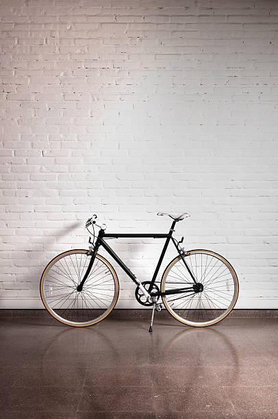 Black bicycle by a white brick wall:スマホ壁紙(壁紙.com)