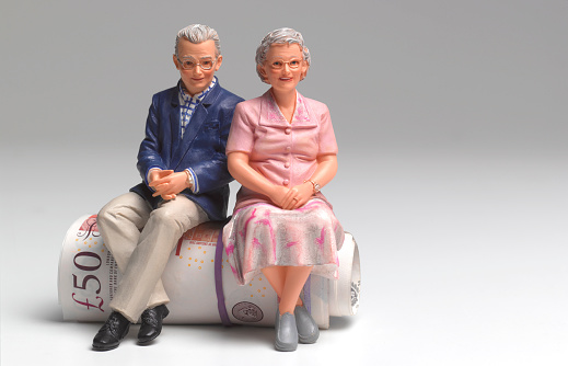 Budget「Retired couple sitting on roll of UK pounds」:スマホ壁紙(8)