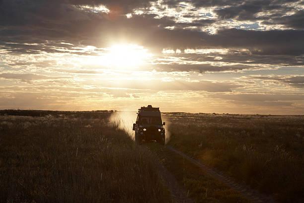 Botswana, four wheel drive car driving across field at sunset:スマホ壁紙(壁紙.com)