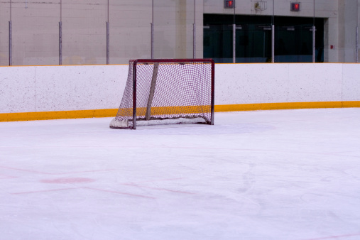 Skating「an ice rink with yellow lines on the wall and a hockey net」:スマホ壁紙(0)
