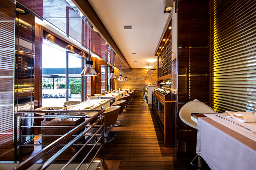Delicatessen「A row of dining tables located next to a wine display shelf in a high profile restaurant interior」:スマホ壁紙(0)