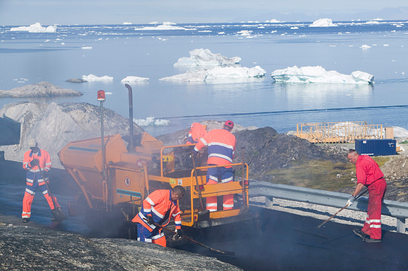 ヤコブスハブン氷河「Laying tarmac on a road in Ilulissat on Greenland with icebergs from the Jacobshavn icefjord behind」:写真・画像(7)[壁紙.com]