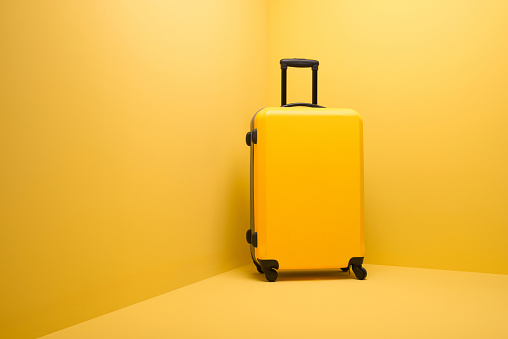 Convenience「Yellow suitcase standing on yellow background」:スマホ壁紙(8)