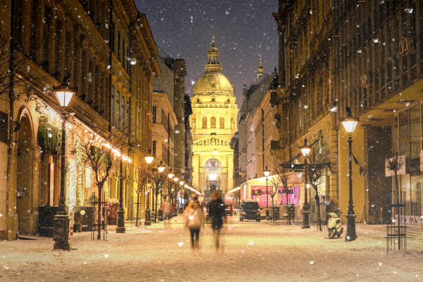 Illuminated cityscape of Zrinyi Street in Budapest with St Stephen's Basilica in a snowy winter landscape at dusk:スマホ壁紙(壁紙.com)