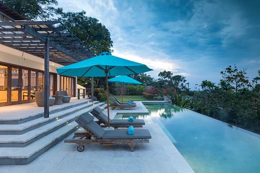 プール「バリ島の夕暮れ時のプールのある照らされた豪華なヴィラ」:スマホ壁紙(1)