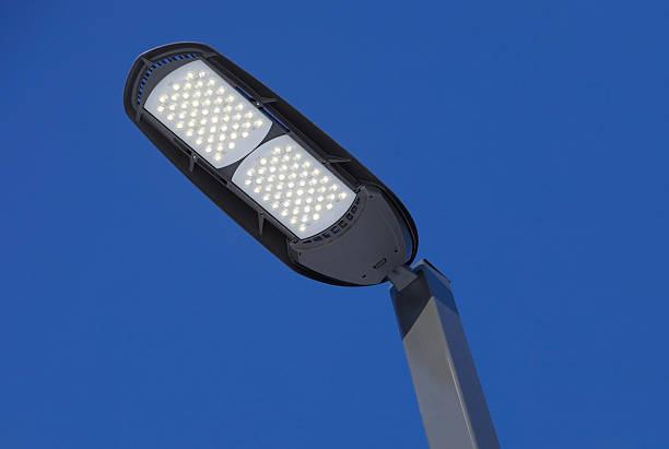 Illuminated LED Streetlight against a Clear Blue Sky:スマホ壁紙(壁紙.com)