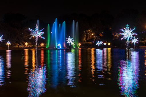 Christmas「Illuminated snowflakes and a spraying water fountain illuminated with colourful lights reflected in water」:スマホ壁紙(6)