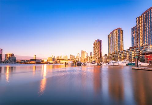 Melbourne Docklands「Illuminated buildings by river at Melbourne Docklands against blue sky at dusk, Victoria, Australia」:スマホ壁紙(5)