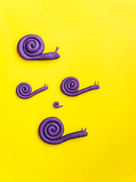Snail family made of modelling clay on yellow background:スマホ壁紙(壁紙.com)