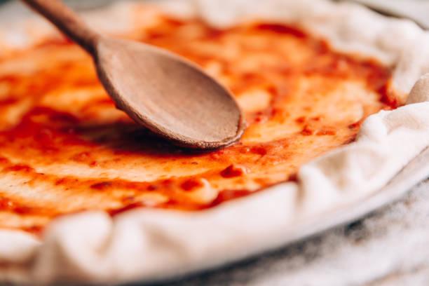 Spreading tomato sauce on pizza pan:スマホ壁紙(壁紙.com)