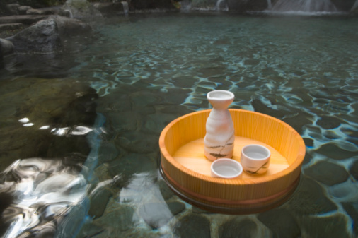 Sake「Sake bottle and cups in a wooden tub floating on a Japanese public bath, hot spring, high angle view, Japan」:スマホ壁紙(13)