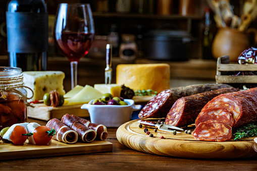 Wine Bottle「Tapas of cheese, cured ham, salami wine and chorizo on a rustic wooden table」:スマホ壁紙(0)