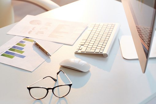 Computer Keyboard「Close-up of business papers with graphs and charts placed on desk with computer, eyeglasses and pen, background」:スマホ壁紙(12)