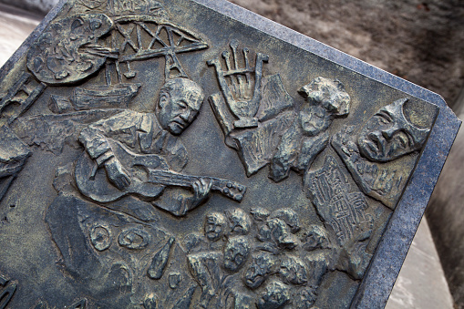 Guitarist「Closeup of very old weathered bronze plaque of man playing guitar and showing artist pallet and crowd on crypt.」:スマホ壁紙(5)