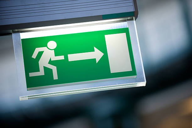 Close-up of green emergency exit light sign:スマホ壁紙(壁紙.com)