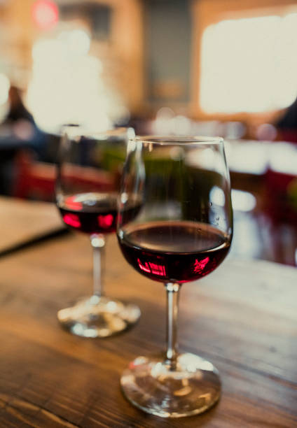 Close-up of two glasses of red wine on a table, shot in natural light.:スマホ壁紙(壁紙.com)
