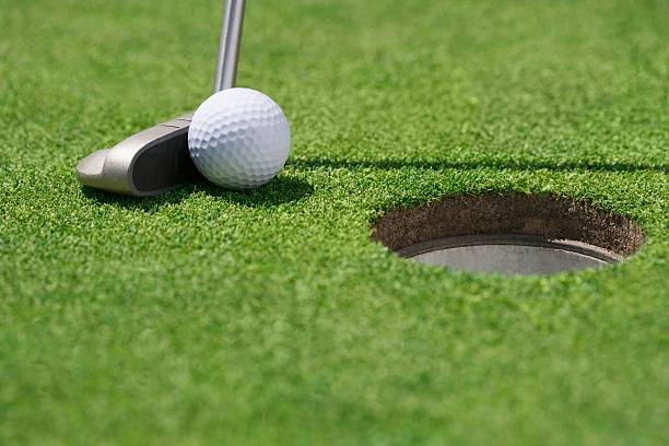 Close-up of golf ball and club near cup:スマホ壁紙(壁紙.com)