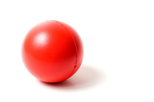 Releasing「Close-up of a red rubber stress ball on white background」:スマホ壁紙(17)
