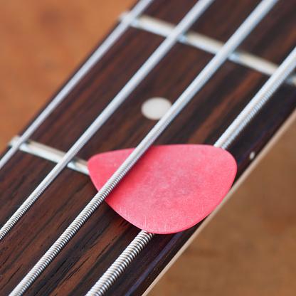Bass Instrument「Close-up of bass guitar with guitar pick」:スマホ壁紙(14)