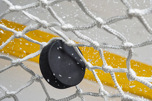 Taking a Shot - Sport「Close-up of an Ice Hockey puck hitting the back of the net as snow flies, front view」:スマホ壁紙(4)
