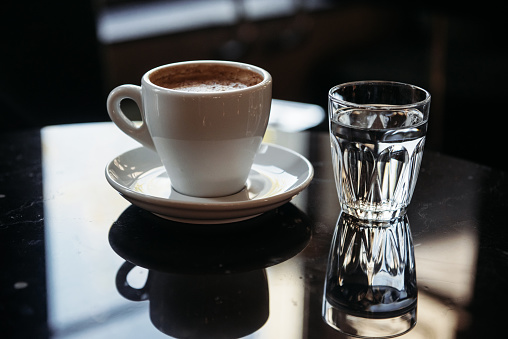 Austria「Close-up of a cup of coffee and glass of water on a table」:スマホ壁紙(14)
