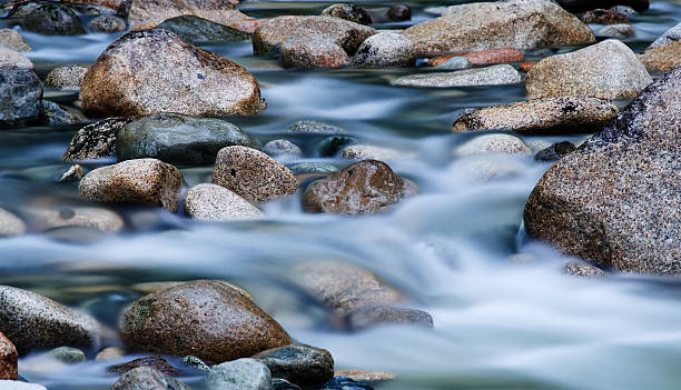 Close-up of clear water flowing through pebbles in stream:スマホ壁紙(壁紙.com)