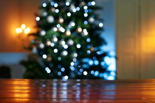 キラキラ「Close-up of wooden table with illuminated Christmas tree in background at home」:スマホ壁紙(2)