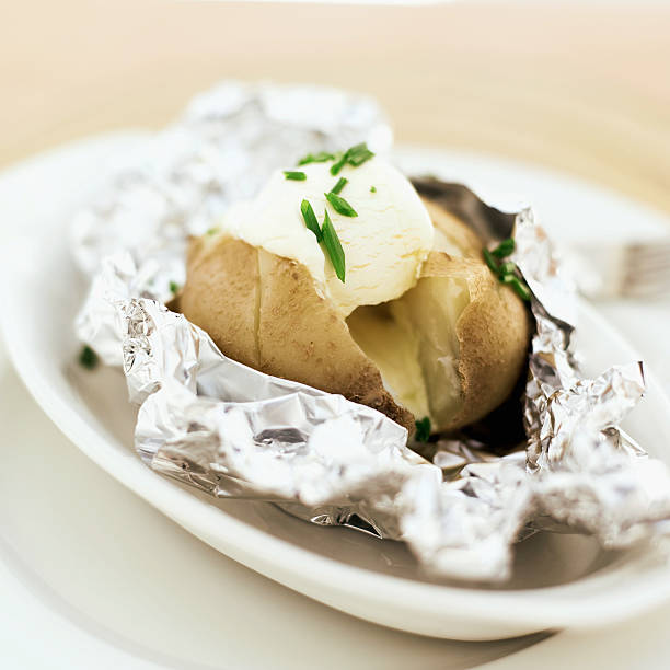 close-up of a baked potato served with sour cream in foil:スマホ壁紙(壁紙.com)