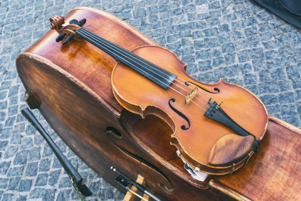 Close-Up of Violin Resting on Double Bass of Street Musicians Against Cobblestone Road:スマホ壁紙(壁紙.com)