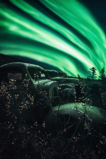 星空「Northern lights overtop of abandoned trucks up the North Canol Road」:スマホ壁紙(4)