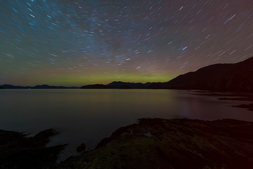 星空「Northern Lights glowing on horizon with star trails, Settlers Cove State Park, Ketchikan, Alaska, USA」:スマホ壁紙(10)