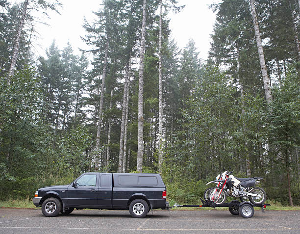 Truck towing motorbikes on trailer in forest, side view:スマホ壁紙(壁紙.com)