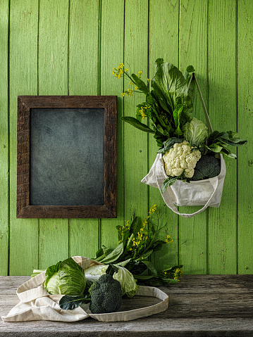 Cauliflower「Leafy green vegetables hanging in a reusable cotton bag, by the side of a blackboard, on an old green wood board wall background, with another bag of greens on a wood table underneath.」:スマホ壁紙(19)