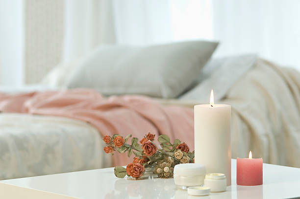 Candles, skin cream and bunch of roses on table with bed in background:スマホ壁紙(壁紙.com)